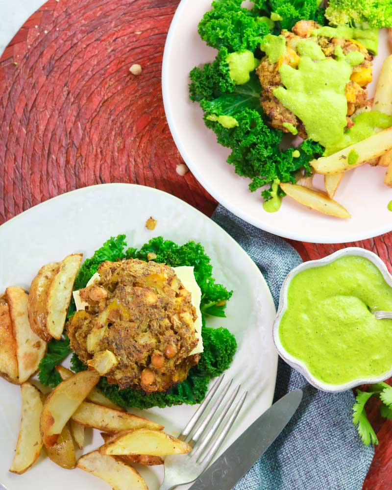 Cauliflower & Chickpea burgers on a plate with big chips and green sauce