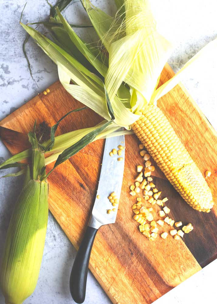 Fresh corn on the cob being cut ready for Corn Fritters