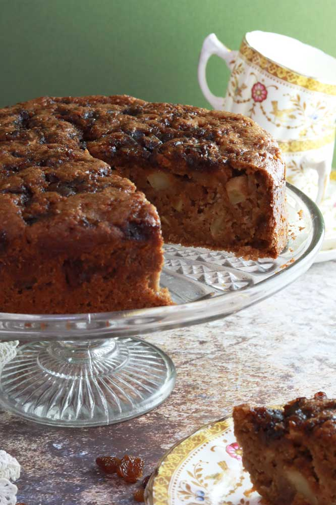 Close up of Vegan Apple and Sultana cake on a stand with slice taken out