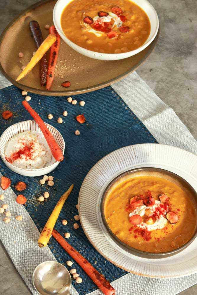 Two bowls of Carrot and Chickpea soup on a table