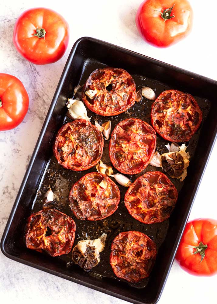 Roasted Tomatoes in a roasting tin with garlic