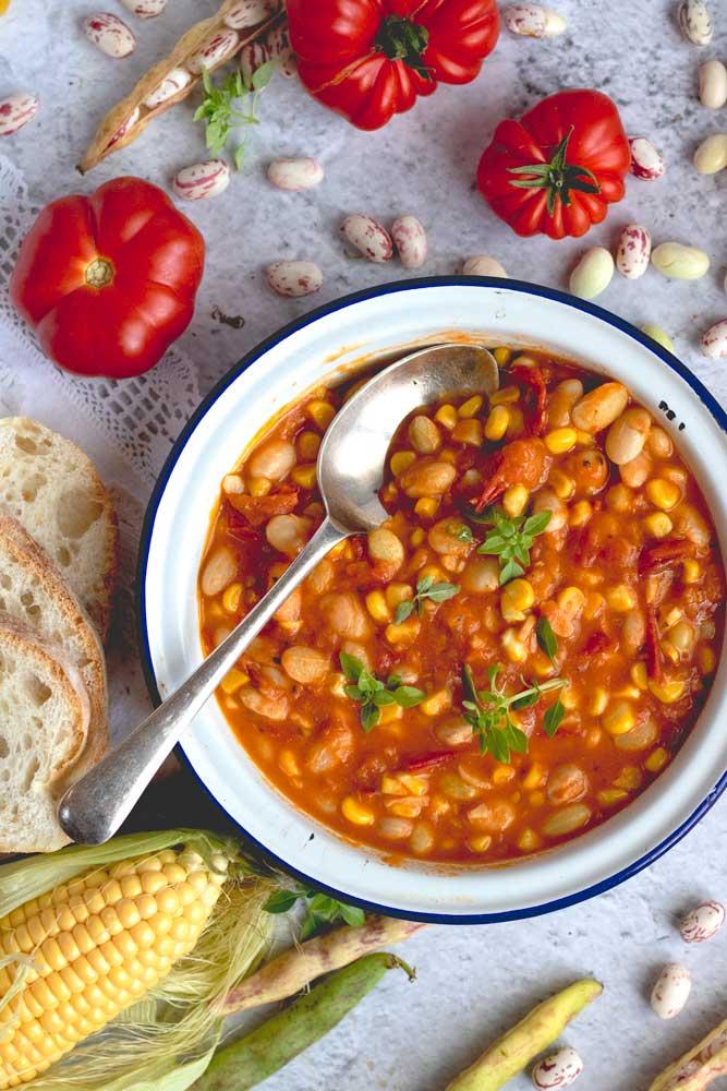 Borlotti, Corn and Tomato stew in a bowl with a spoon