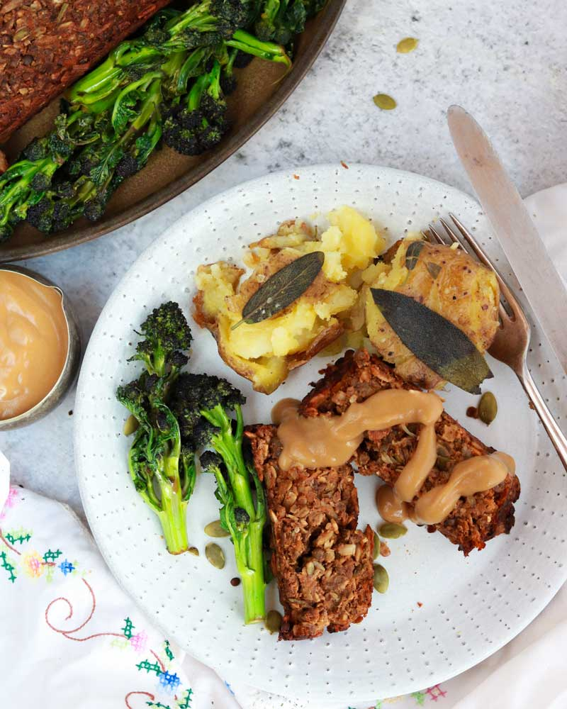 Vegan lentil and seed nutless roast on a plate with potatoes with purple sprouting broccoli