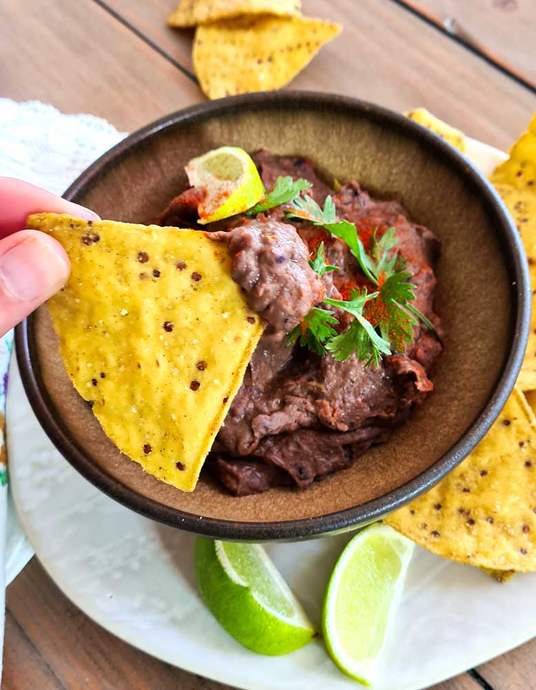Black Bean dip being scooped up with a corn tortilla chip