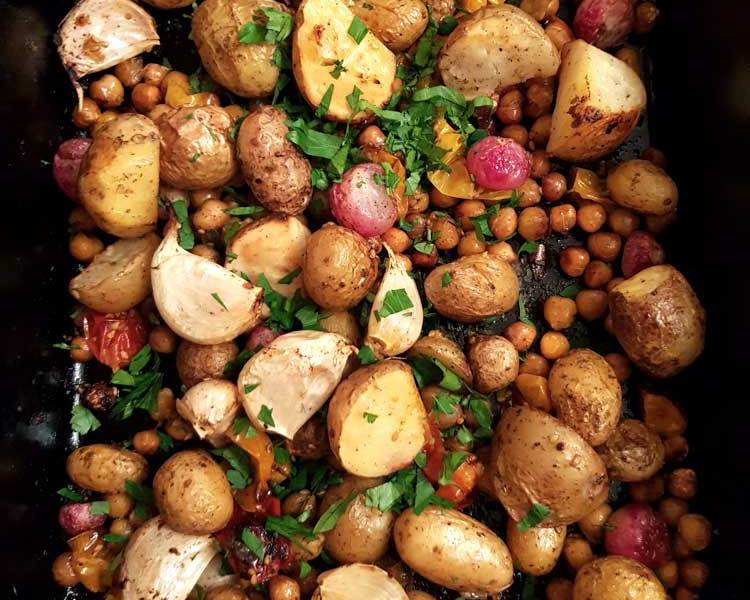 Vegan traybake of potatoes, garlic, chickpeas and radish in a baking tin