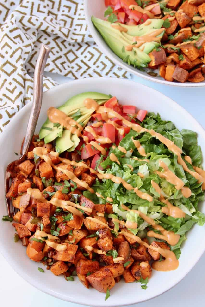 Vegan buritto mix in a bowl with salad and dressing