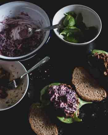 Eine Scheibe Brot, dann Babyspinat, dann Jackfruit , dann Krausalat gefolgt von einer zweiten Scheibe Brot als Deckel