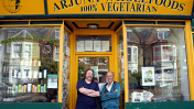 Two men in front of a yellow-painted wholefoods shop.