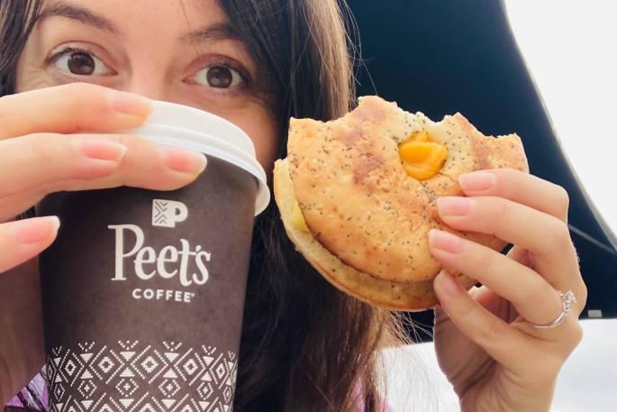 The veggan, Gina, holding Peet's vegan breakfast sandwich and a small vanilla oatmilk latte.