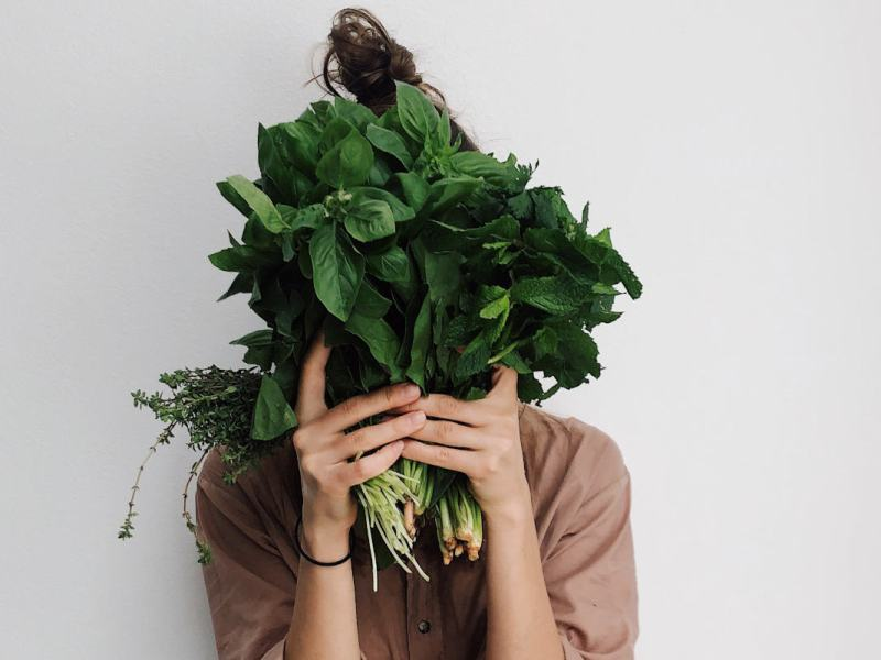 Women with brown hair and tan shirt holding bunches of spinach and herbs in front of her face.