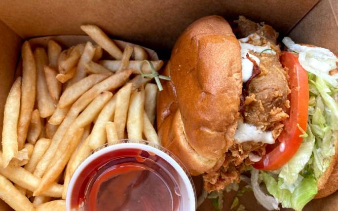 Atlas Monroe Fried chicken sandwich in to-go box with ketchup and fries.