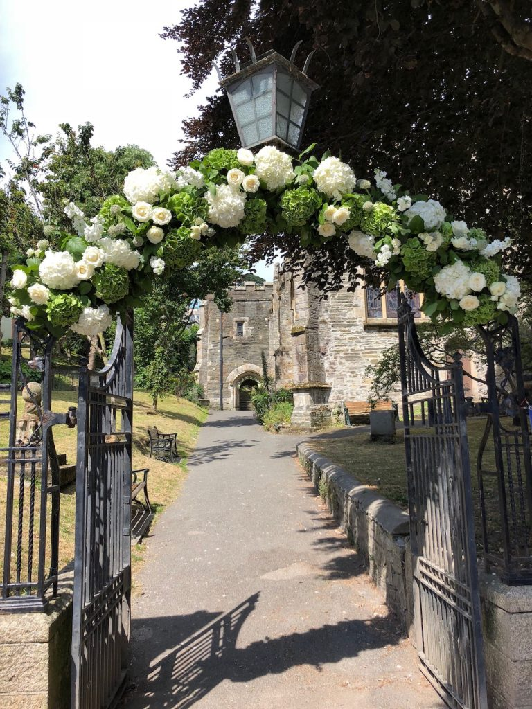 A large green and white hydrangea and rose flower arch over lichgate going into church. A real summer seaside wedding in Cornwall.