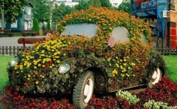 Green Volkswagen Beetle Covered in Flowers