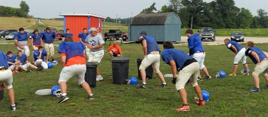 student athletes practice football drills