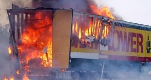 A semi-truck trailer fully engulfed in flames
