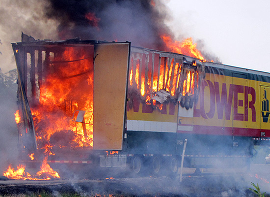 A semi-truck trailer fully engulfed in flames