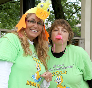 Duck Race coordinator Robin Harper-Whitehead, left, and volunteer Pam Morris pose for a picture as the ducks are just about to leave the starting gate at the Seventh Annual Heather Treat Memorial Duck Race held at Bella T Winery Sunday afternoon.  More than 3,000 ducks were sold and helped to raise $18,000 for Johnson County cancer patients through the Memorial Fund.