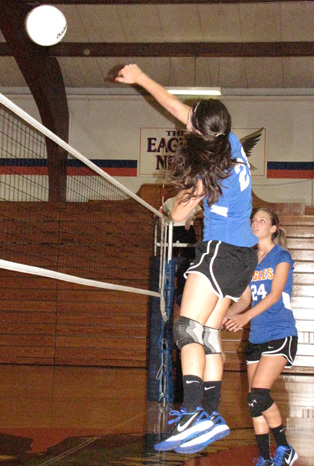 Maranda Chance goes for a kill against Johnston City as Becky Reeder looks on.