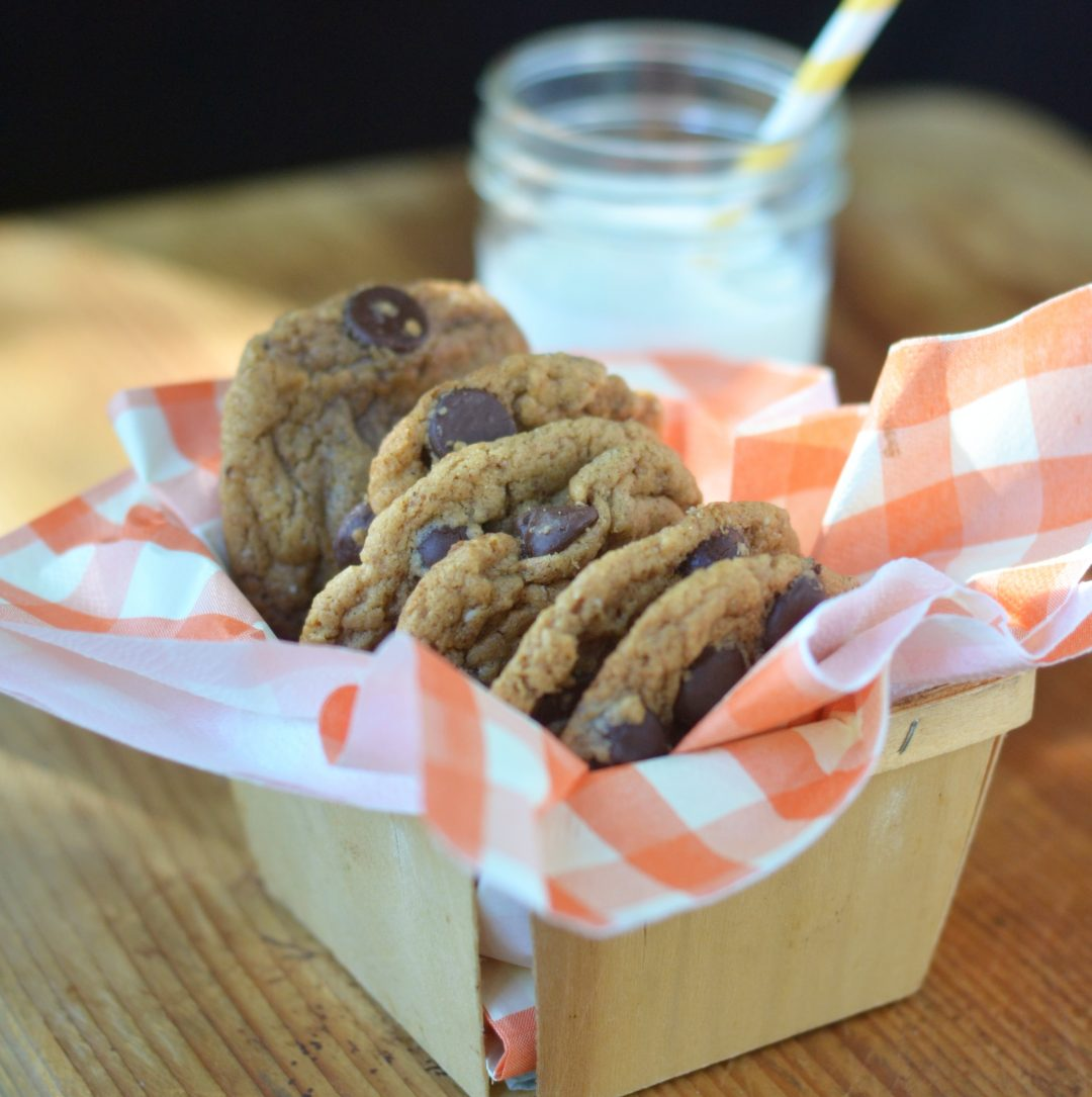 Photo of Flourless Almond Butter Chocolate Chip Cookies in a basket on a wooden surface.