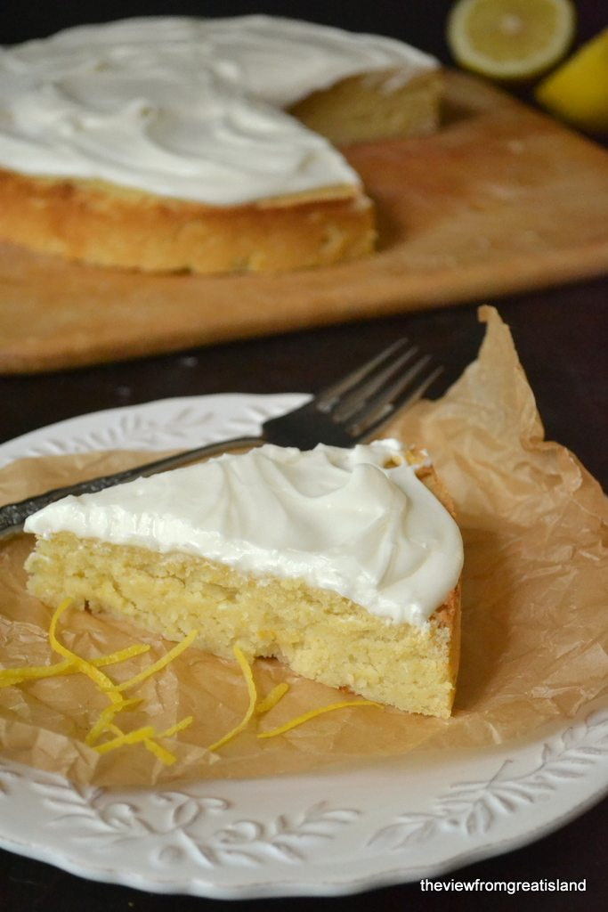 Photo of a slice of flourless whole meyer lemon cake on a piece of parchment paper with a fork.