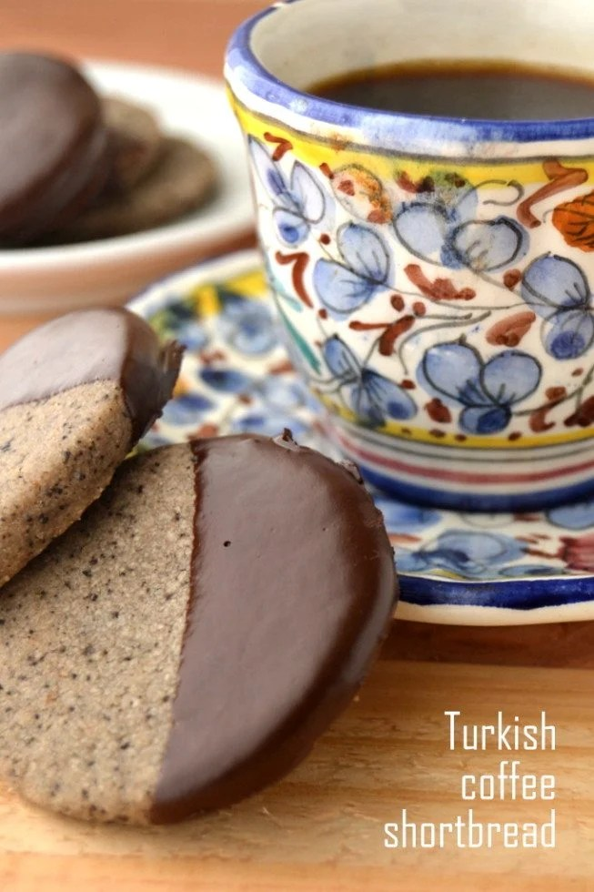 Photo of turkish coffee shortbread cookies next to a patterned teacup and saucer.