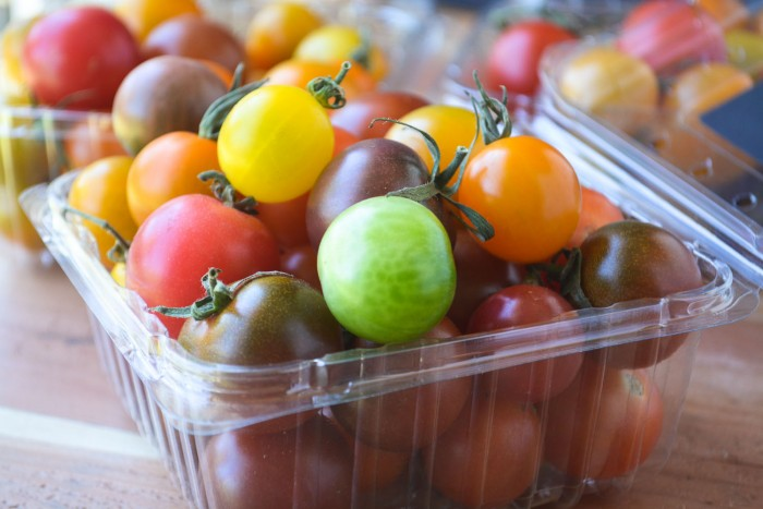 multi-colored cherry tomatoes in plastic tubs