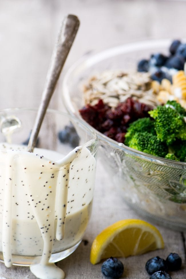 Dressing a colorful and gluten free Broccoli and Blueberry Pasta Salad with Lemon Buttermilk Dressing