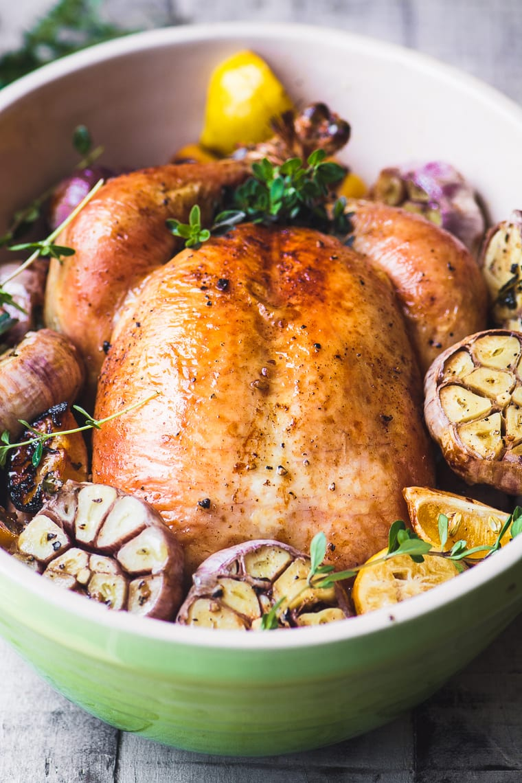 a whole roast chicken with purple garlic in roasting pan