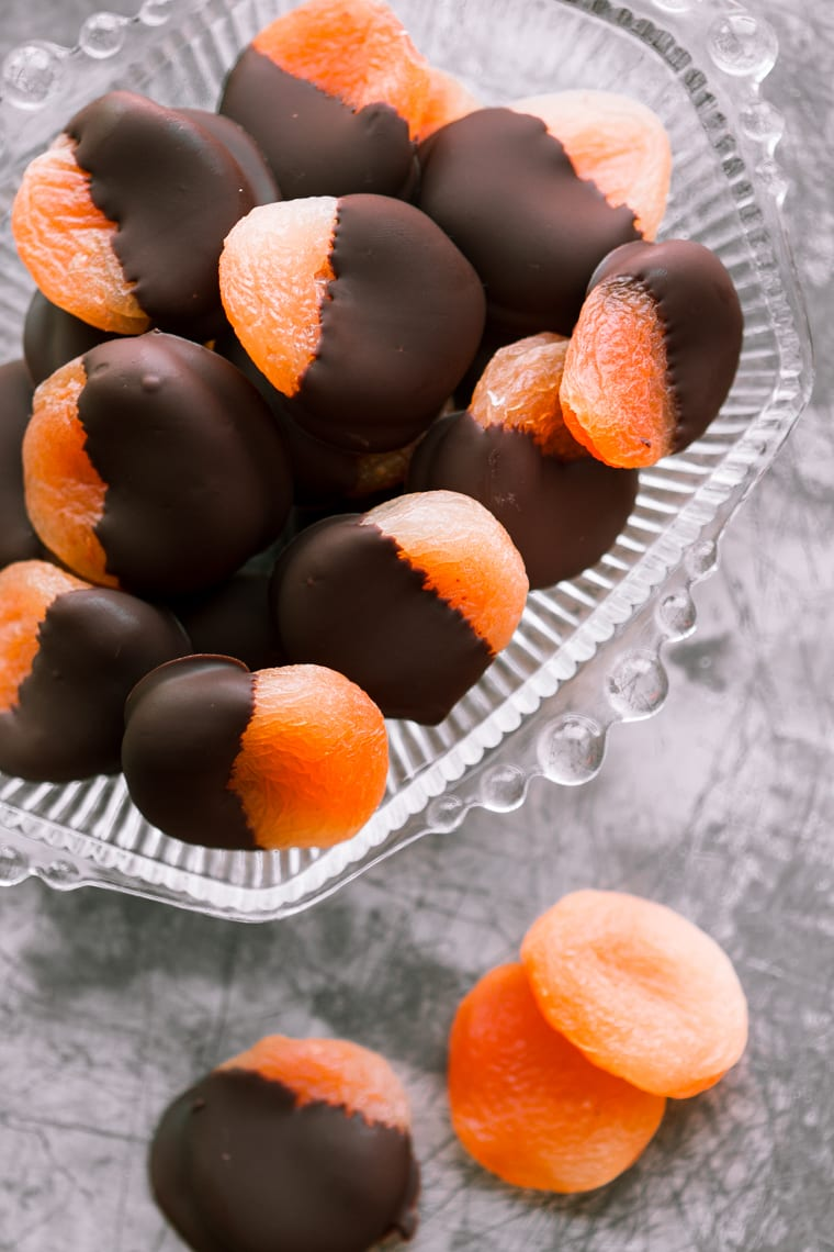 chocolate dipped apricots in a glass bowl