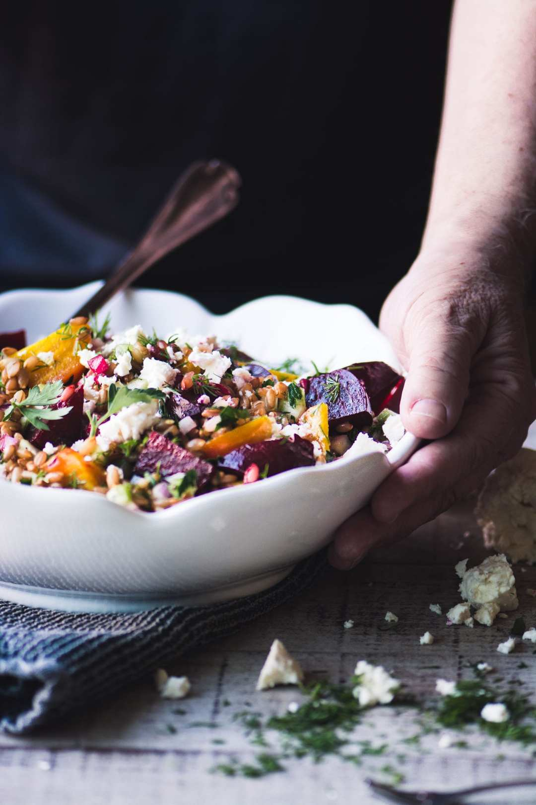 wheat berry salad with beets in a white bowl with spoon