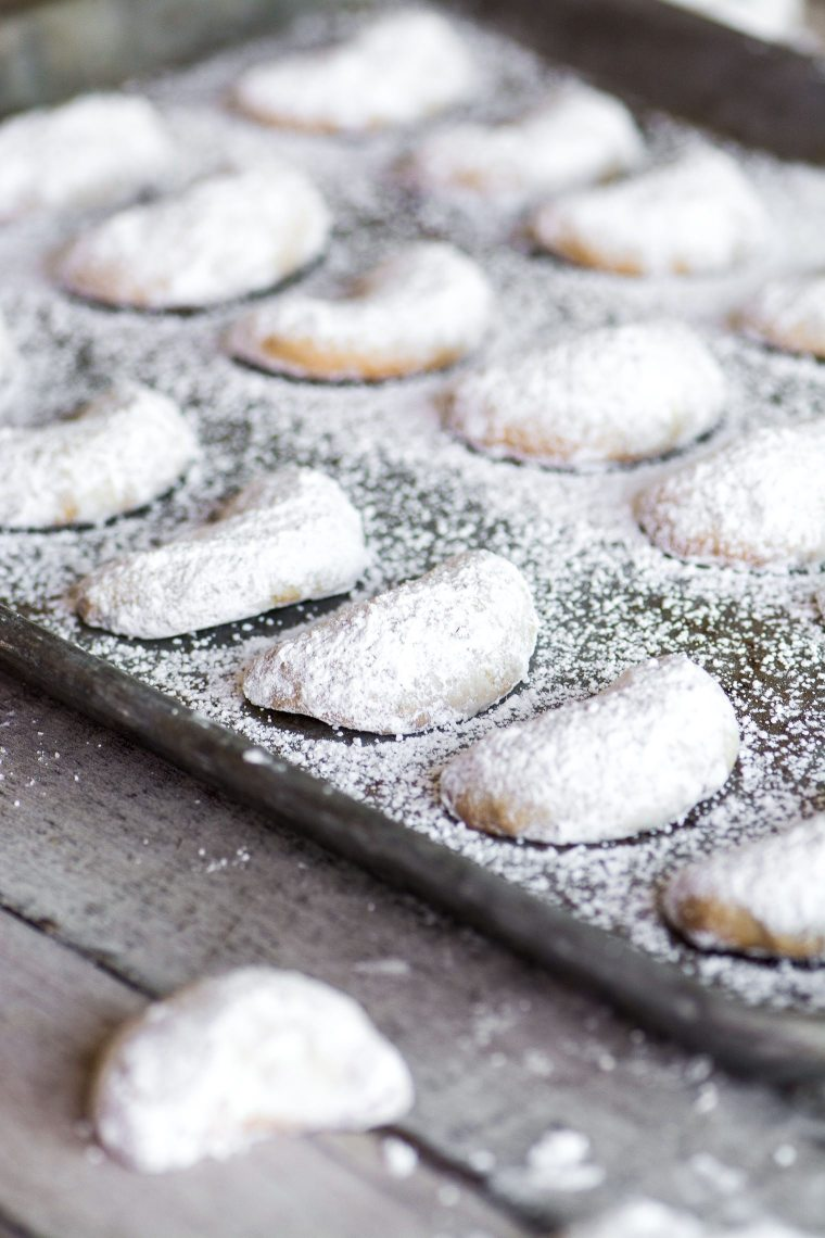walnut crescent cookies on a baking sheet