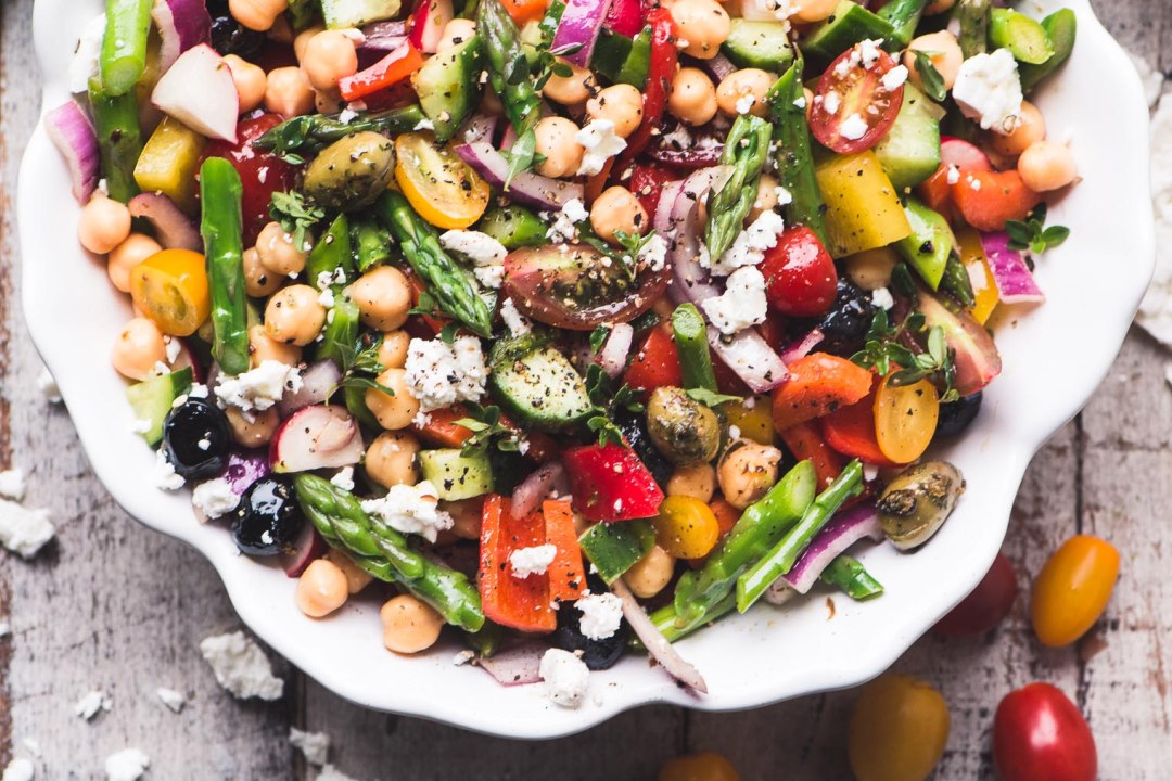 Chopped Asparagus Salad in a white bowl on a wooden table 2