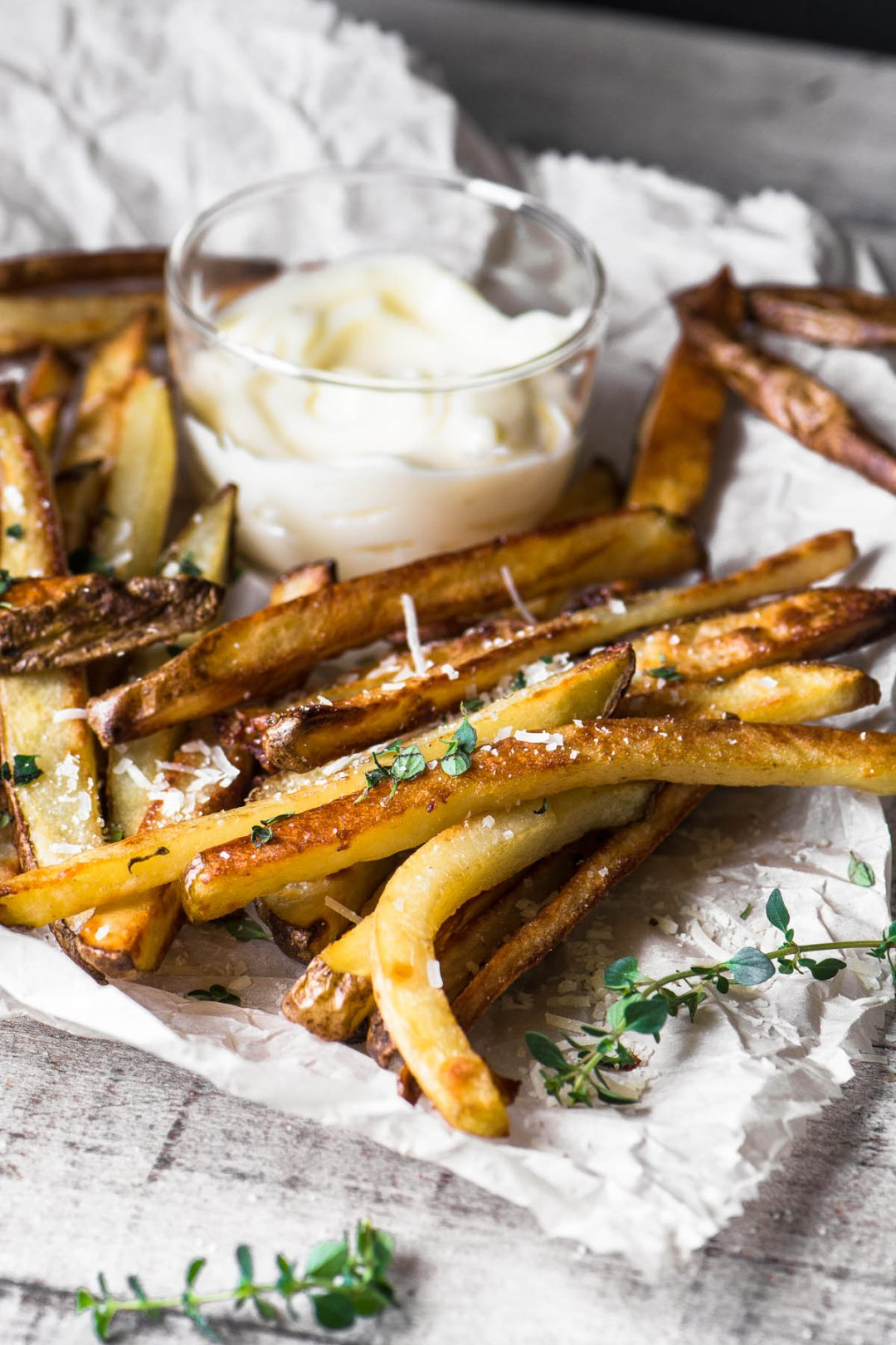 Baked truffle fries on a parchment paper with truffle mayo for dipping