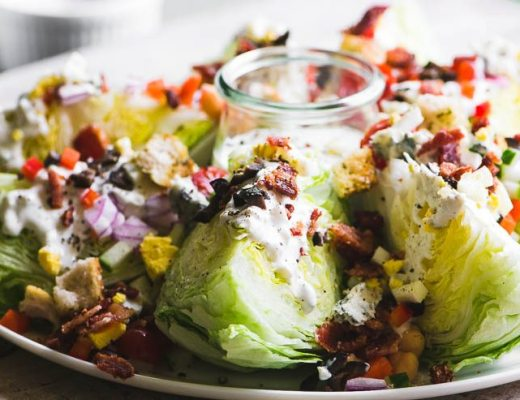 Fully Loaded Wedge Salad on a platter with dressing