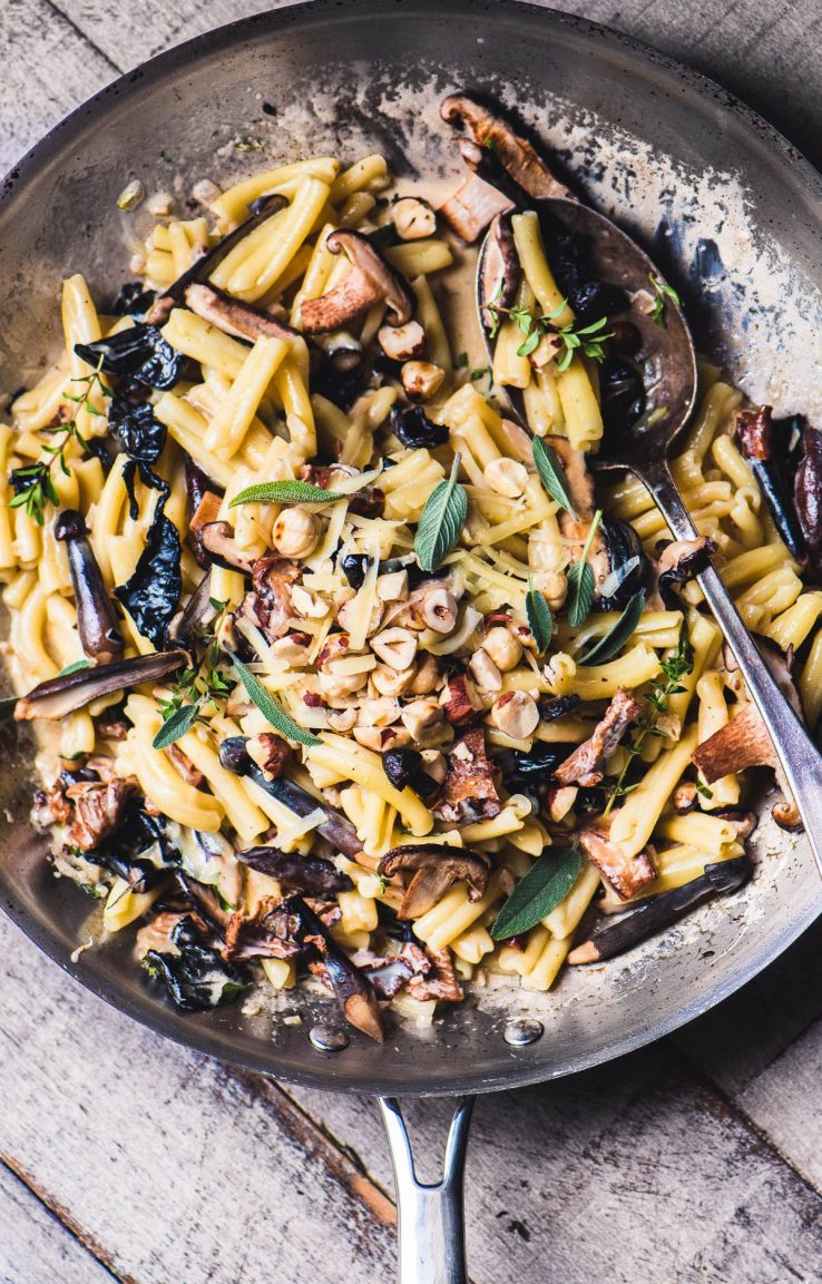 Pasta with wild mushrooms and hazelnuts in a skillet with large spoon
