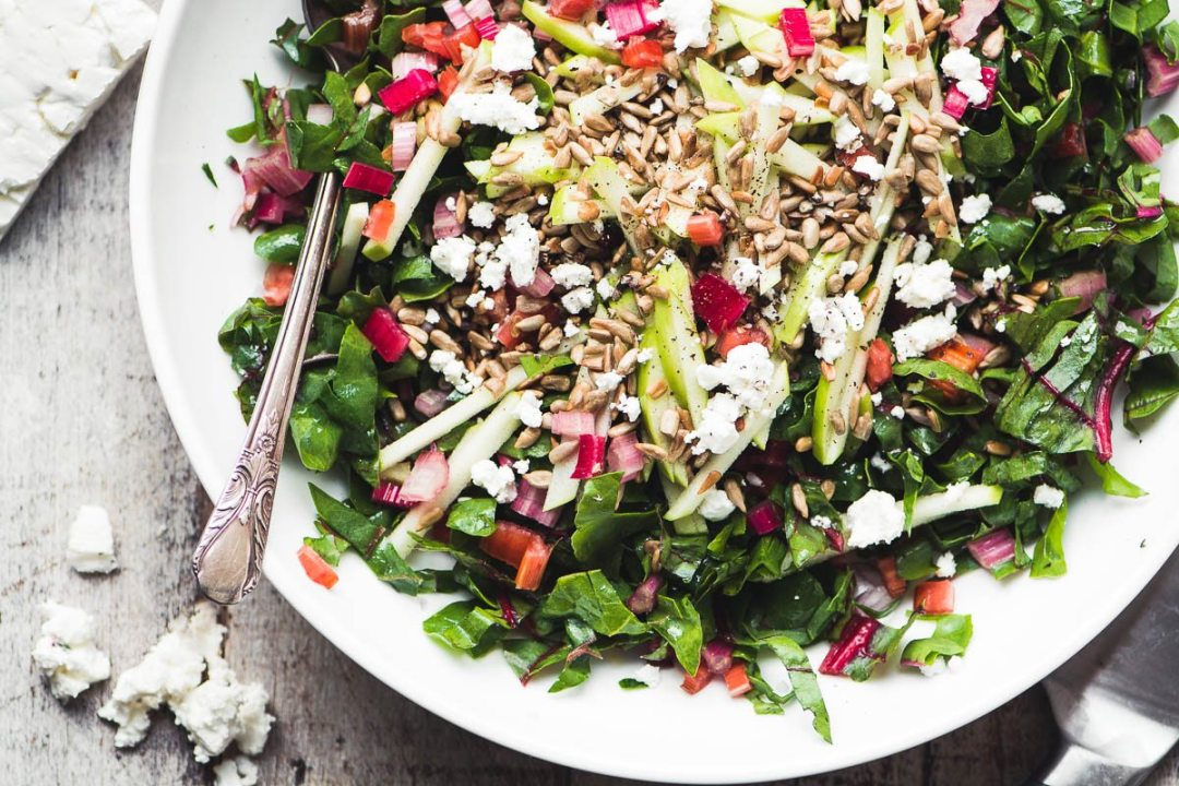 Rainbow Chard Salad in a white bowl with spoon