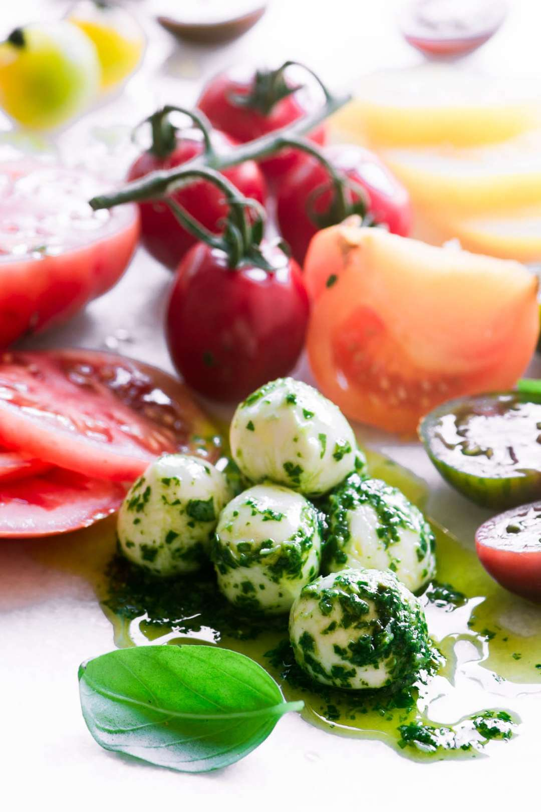Basil marinated mozzarella with heirloom tomatoes on a white surface