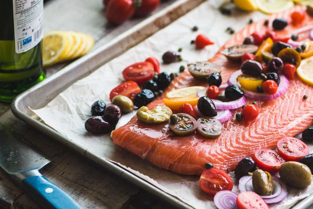 Preparing Mediterranean Roasted Sheet Pan Salmon for baking