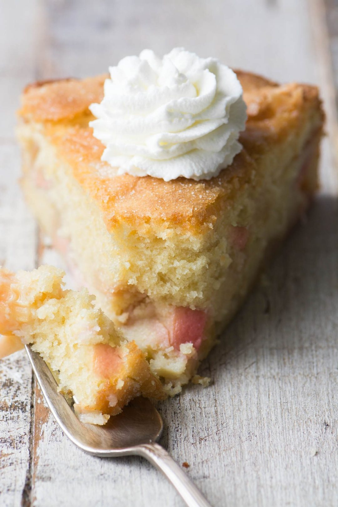 A slice of peaches and cream breakfast cake with whipped cream and fork