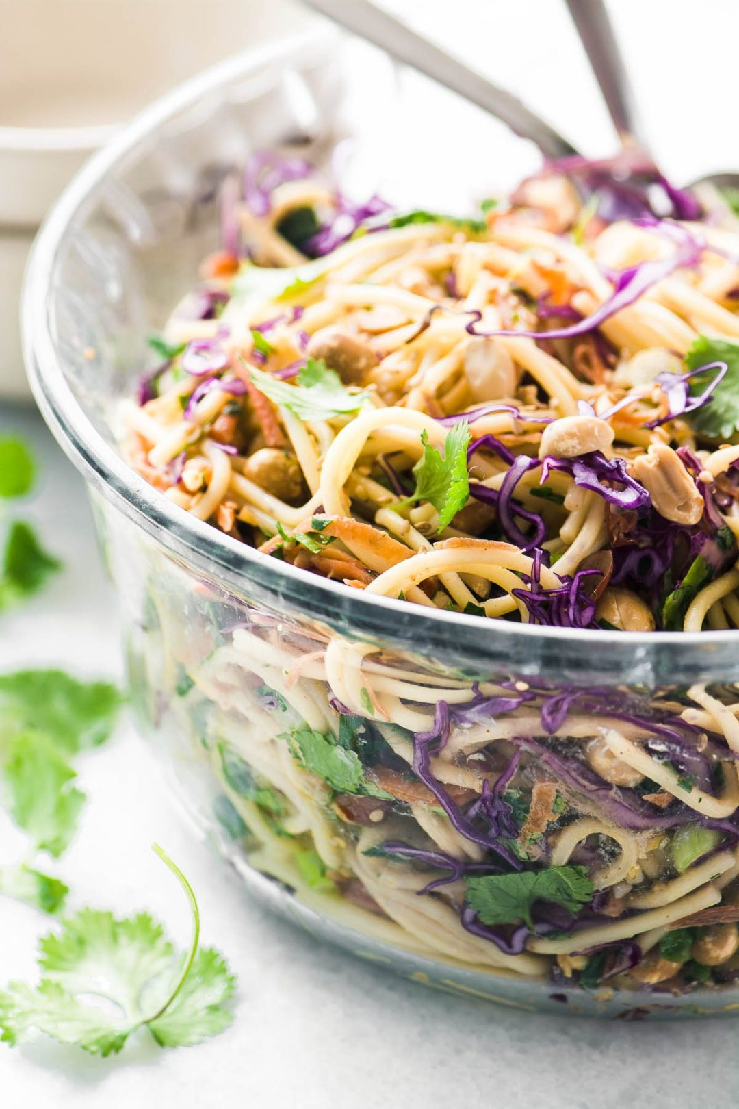 A spicy Thai spaghetti salad in a glass bowl with cilantro leaves