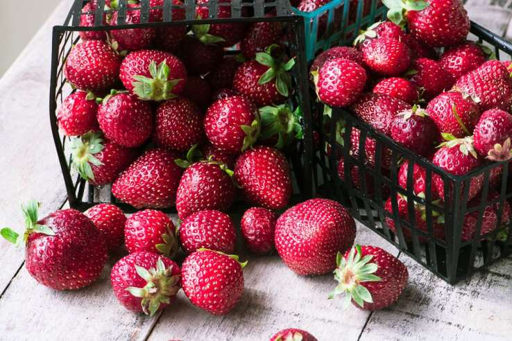 baskets of strawberries spilled onto a wooden surface