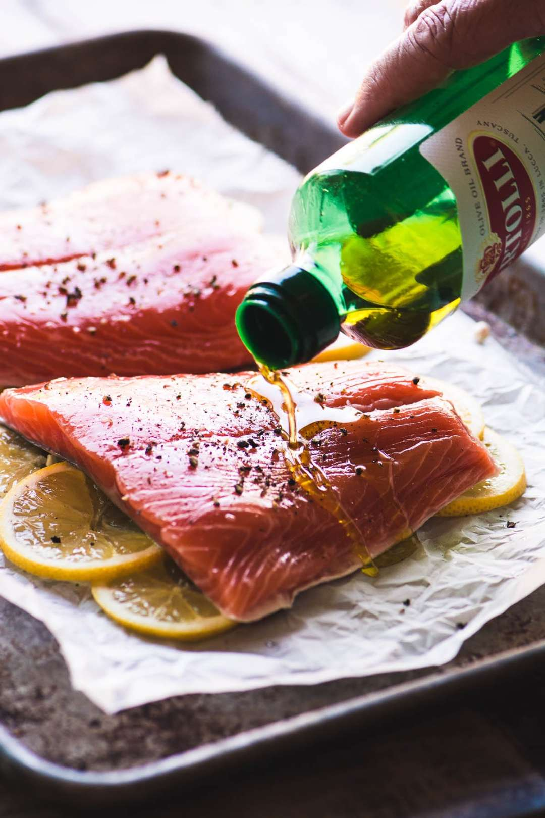 salmon on a sheet pan with lemons ready for the oven