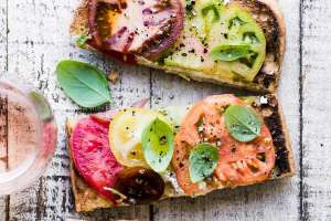 Colorful heirloom tomato toast with glass of rosé wine