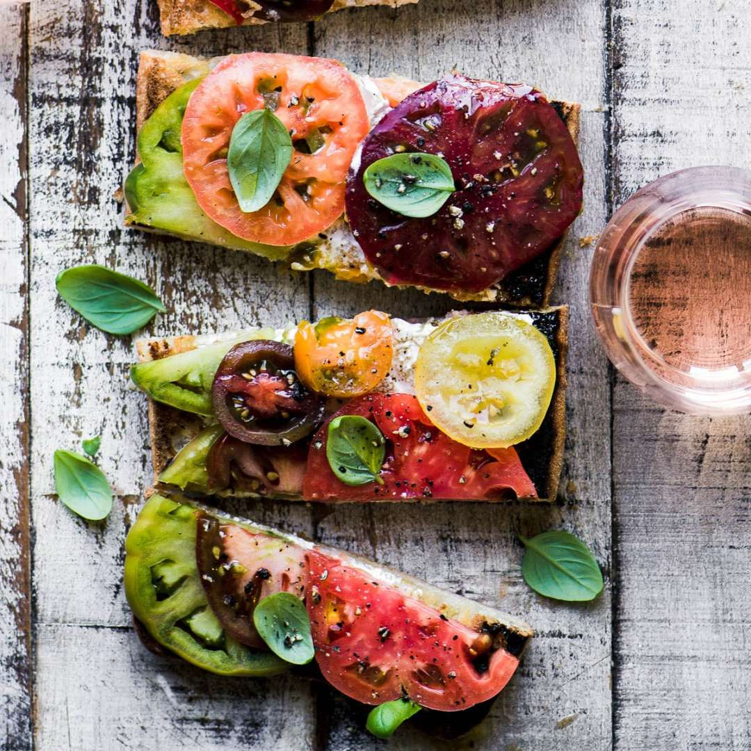 Colorful heirloom tomato toast on a wooden table with glass of rosé wine