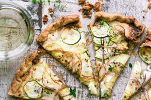Savory goat cheese and summer squash tart sliced on a wooden table with a glass of wine