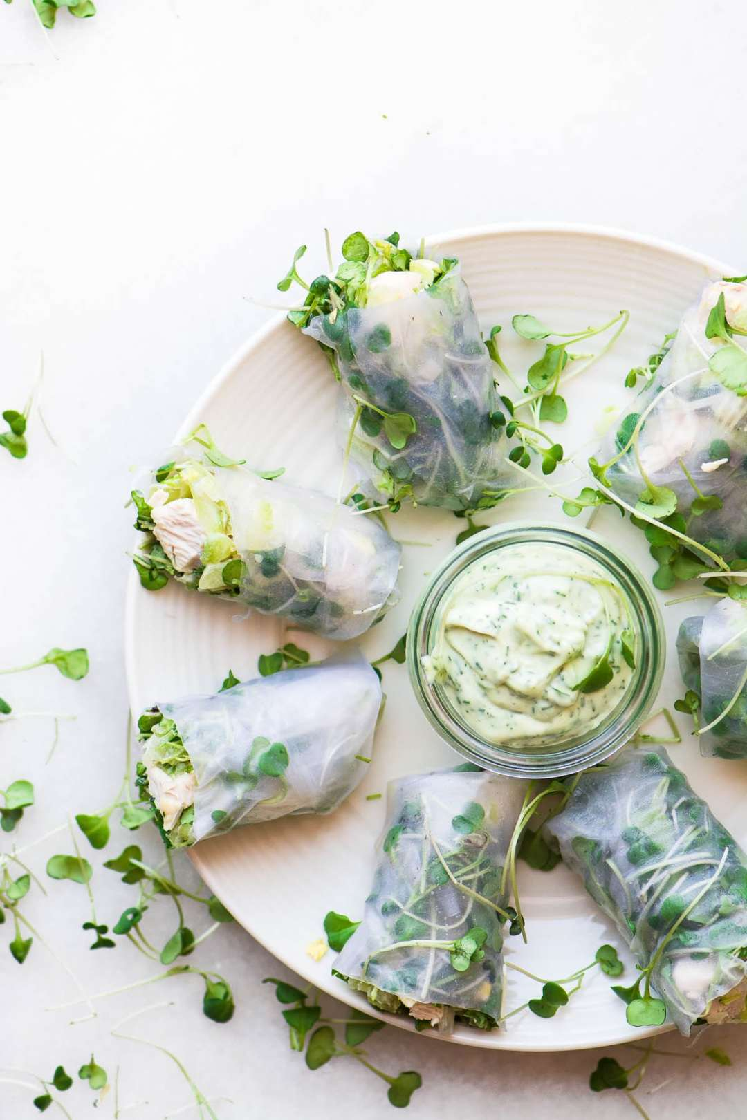Chicken Salad Summer Rolls on a white platter with herbed mayo dip