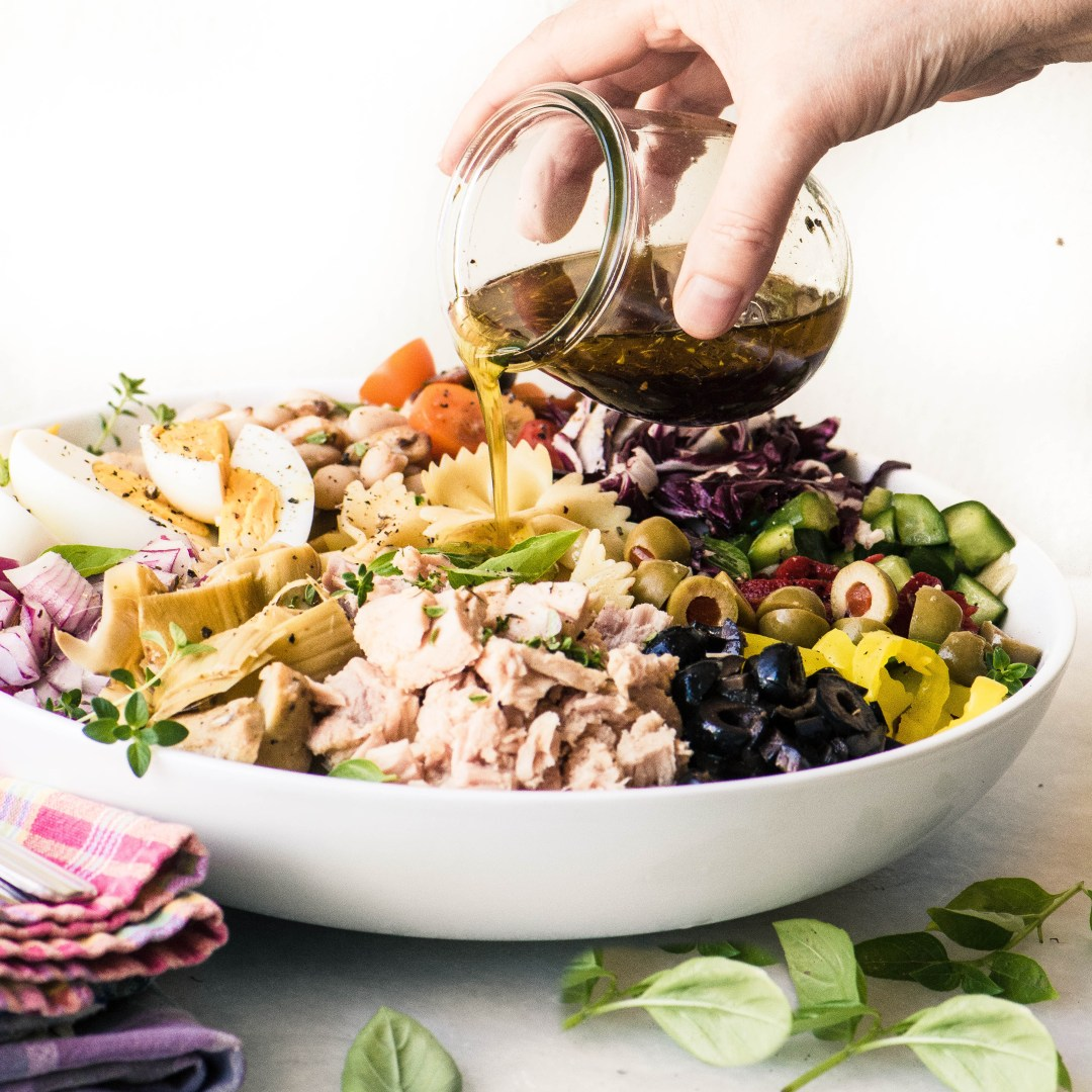 Pouring Italian dressing on a Mediterranean Pasta Salad with Tuna