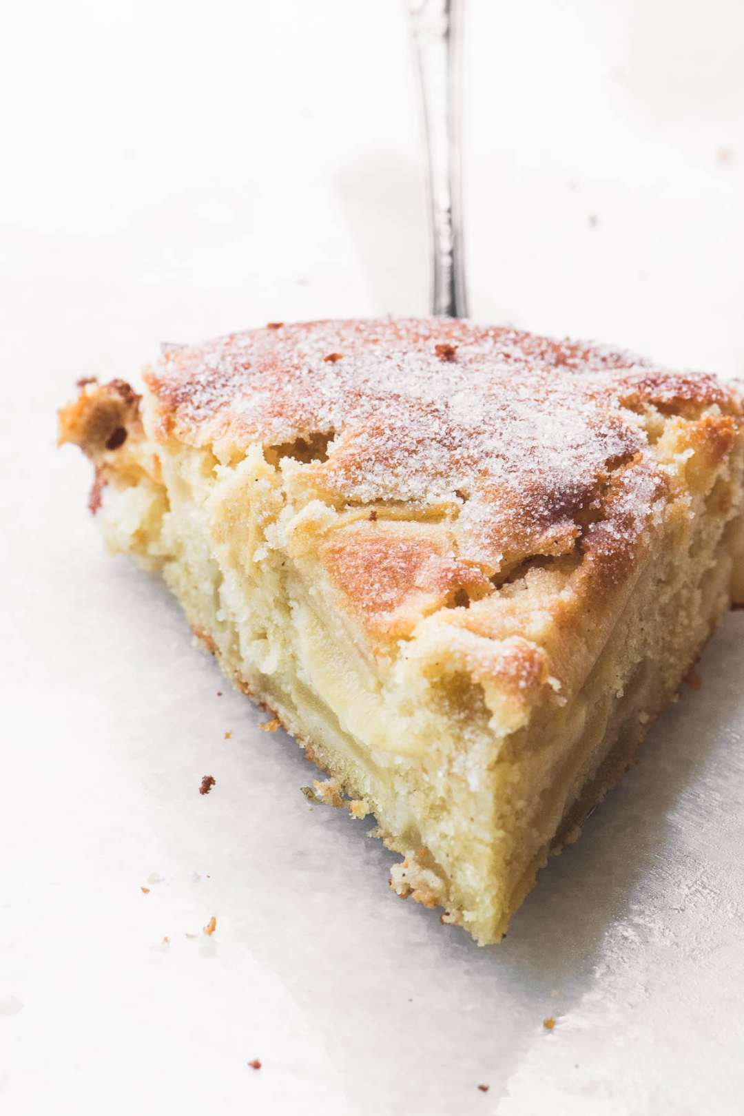 A slice of Dutch Apple Cake on a silver pie server on a white marble ground