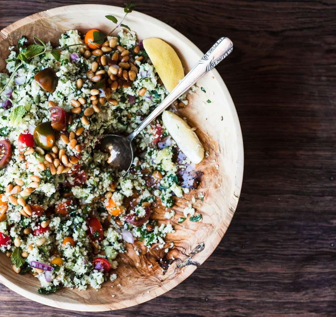 Cauliflower Rice Tabbouleh in a wooden bowl with spoon