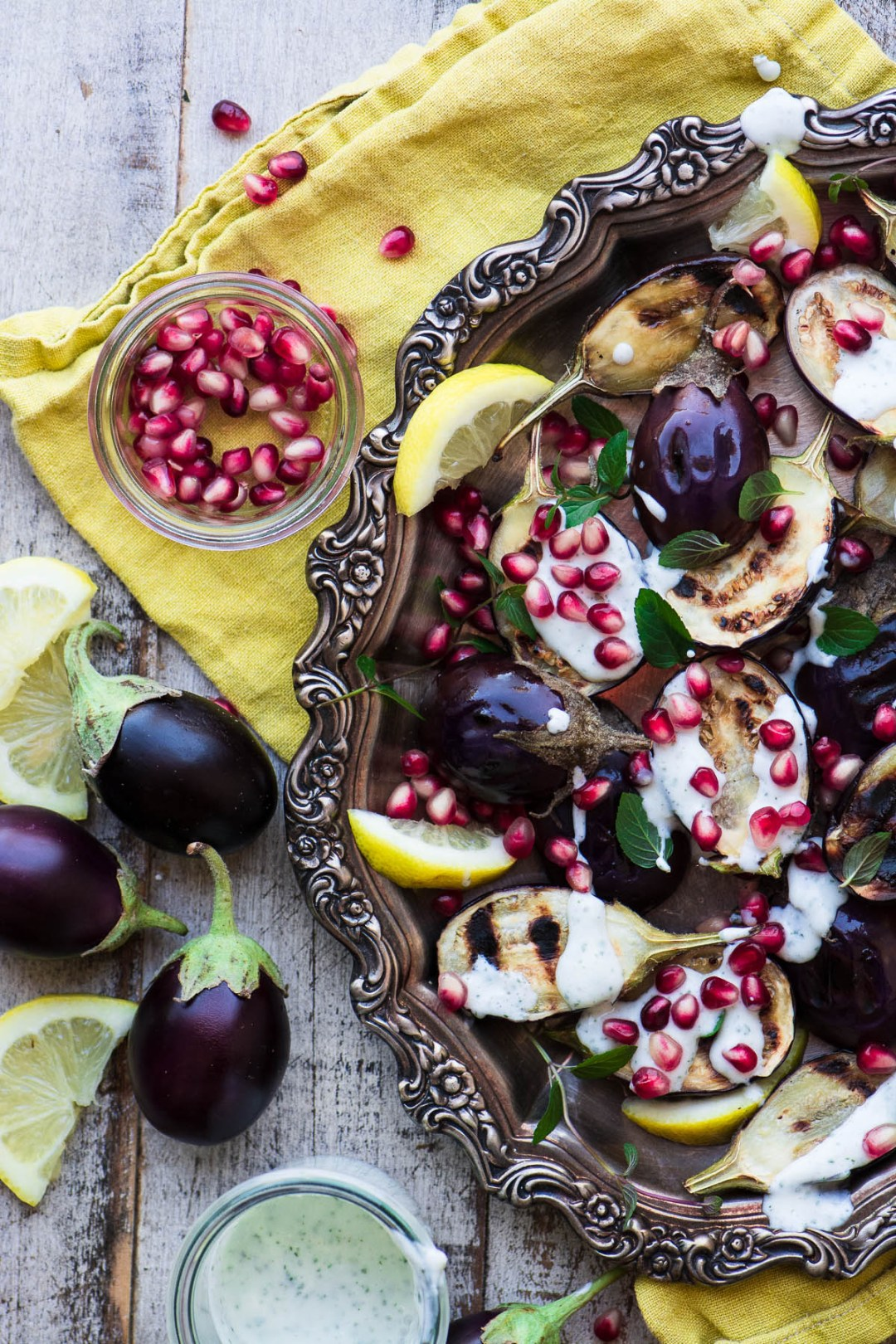 Grilled Baby Eggplant with Minted Yogurt and Pomegranate on a silver tray with napkin and a bowl of pomegranate seeds